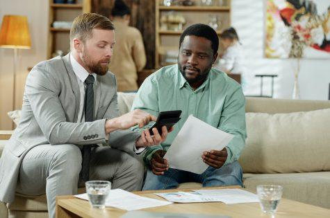 Diverse men calculating loan rate